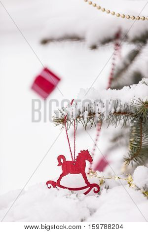 Christmas decorations on a beautiful tree with snow outdoors. Season holidays and celebrations. Traditional Christmas tree decor.