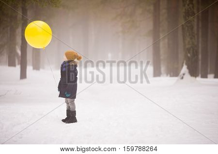 A small boy holding a big yellow balloon in the winter forest. Birthday boy with balloon. Winter walks with snow.