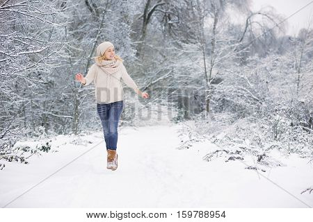 Happy young woman running and having fun in a winter park. Holidays and Christmas concept. Girl outdoors.