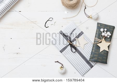 Top view on nice Christmas gifts packed in black and striped paper and decorated with stars on wooden background. Presents and decor elements. Holidays and winter concept.