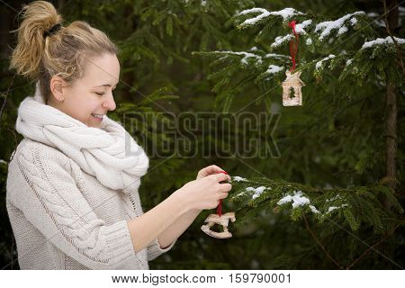 Portarait of young smiling woman decorating Christmas tree with retro wooden toys. outdoors. Celebration winter and holidays concept.