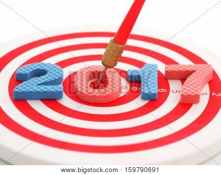Year 2017 goal two thousand seventeen with blur red bullseye dart arrow hitting target center dartboard in background. Happy New Year.