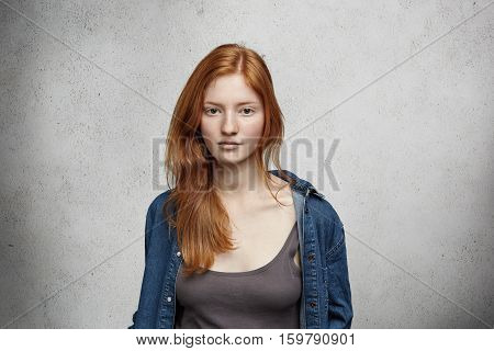 Portrait Of Young Redhead Caucasian Woman With Freckles Dressed In Denim Shirt Over Top Posing Isola