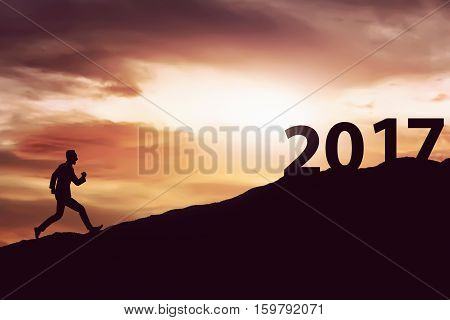 Image of silhouette man running on the hill toward 2017