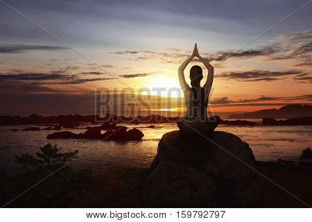 Woman sit over the rock doing yoga on the beach