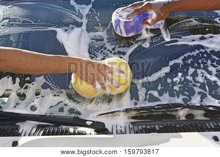 Two men washing windshield, close up of hands
