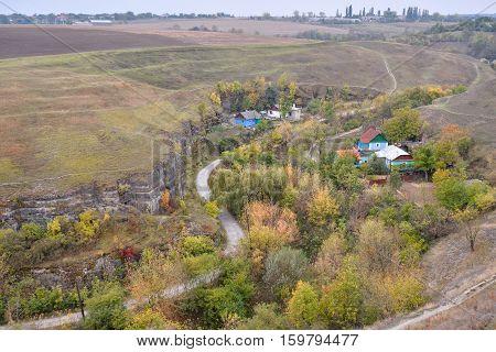 Kamenets-Podolsky, Khmelnitsky region, Ukraine - October 10, 2016: Little village and Smotrichsky canyon in Khmelnitsky region, Ukraine. Beautiful rural fall landscape and canyon