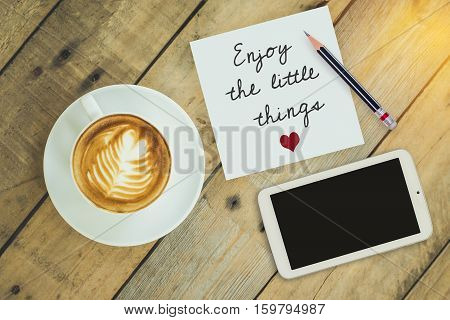 Top view of coffee cup on wooden table with paper note
