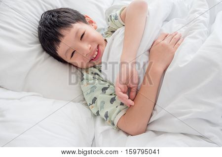 Young Asian boy smiles after waking up in bed