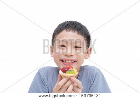 Young Asian boy eating fruit tart over white background