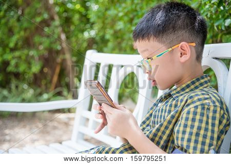 Young asian boy playing game on smart phone