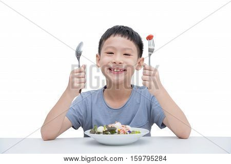 Young asian boy eating vegetables salad over white