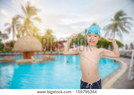 Young asian boy smiling at swimming pool