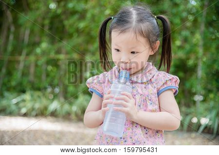 Little asian girl drinking water from bottle by straw