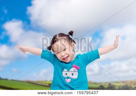 Happy little Asian girl on the field with sky background