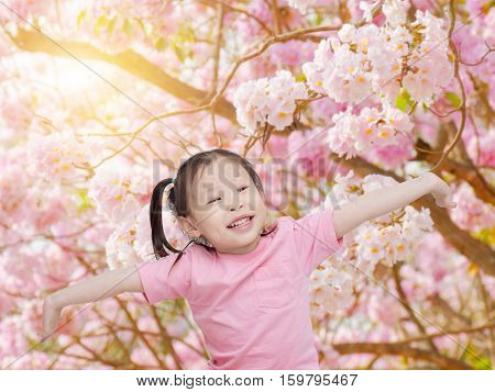 Happy little girl with beautiful pink flower blooming