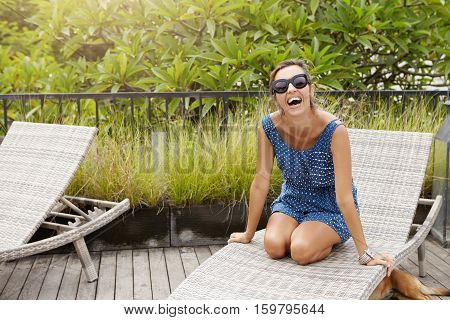 People, Lifestyle And Leisure. Young Pregnant Woman Sitting On Sunlounger Looking And Laughing At Ca