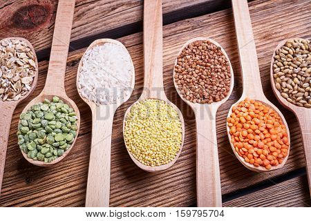 Grains in the spoon, a wooden spoon, a range of cereals, a table of old wood, the grain harvest, organic food, cereal close-up, texture of old wood, kitchen utensils, healthy food