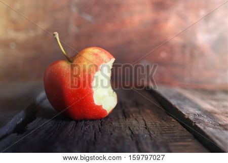 bitten off a little red apple on an old worn wooden background