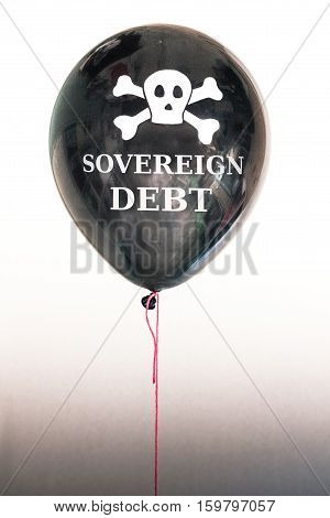 The words sovereign debt and a skull and cross bones on a balloon illustrating the concept of a debt bubble, sovereign debt default, US, EU and other nation state country debt.