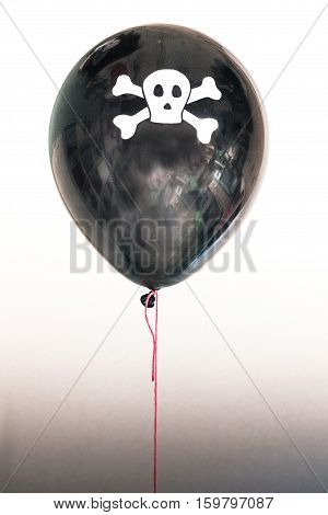 A balloon with a skull and cross bones illustrating the concept of a pirate ship, piracy, death and the jolly roger.