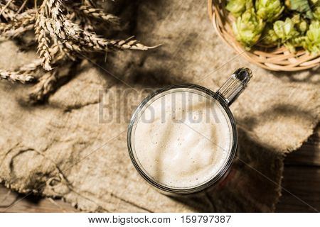 Two tankard beer with wheat and hops on linen cloth on wooden table