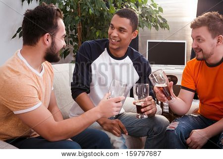 Image of happy friends spending their free time all together by drinking beer at home. Handsome men communicating and speaking about girls.