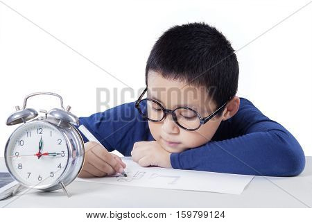 Little schoolboy studying and drawing on the paper with alarm clock on the table isolated on white background