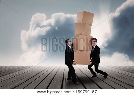 Teamwork conceptual photo: two businessmen carrying stack of boxes