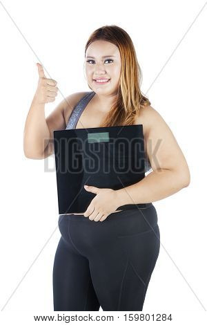 Happy fat woman showing ok gesture with her thumb while holding weight scale isolated on white background