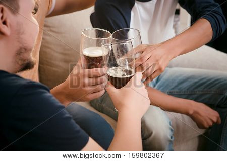 Image of friends drinking beer at home while sitting on sofa or couch. People spending weekends all together. Football match concept.