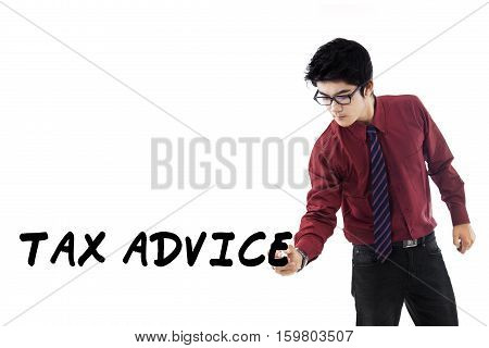 Handsome entrepreneur as a tax consultant writes a text of tax advice on whiteboard isolated on white