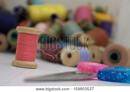 Multi-colored thread and scissors on a white background.