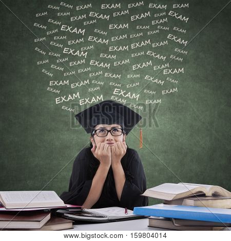 Portrait of female student with gown biting her nails and looks nervous to face exam