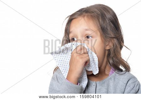 Portrait of sick little girl holding handkerchief isolated on white background