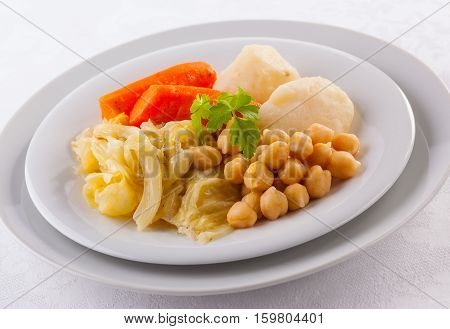 Cocido Madrileño is a delicious Spanish stew with chickpeas sausages potatoes cabbage and various types of meat.