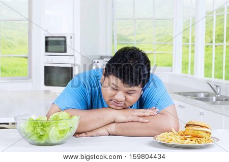 Confused person to choose food looking at a bowl of salad and avoid junk food in the kitchen