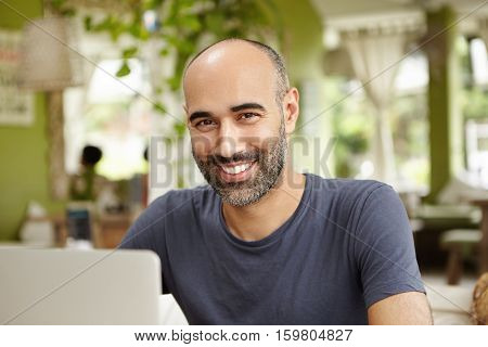 Joyful Freelancer Dressed In Casual T-shirt Sitting In Front Of Laptop, Looking And Smiling At Camer