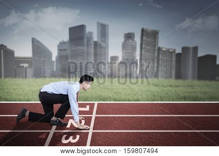Photo of a middle eastern businessman kneeling in start position on the red track