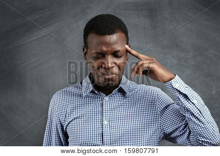Stressed African Businessman With Painstaking Expression Struggling To Remember Something, Closing H