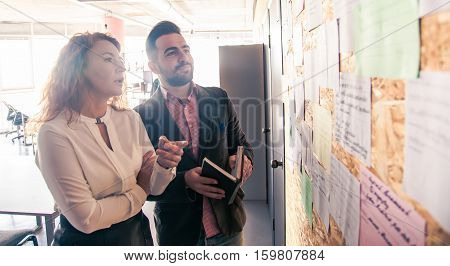 Businessman and businesswoman communicating while standing near notice board in office. People discussing following meetings in board room soom.
