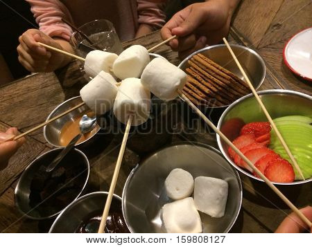 Party mamellow with chocolate and caramel fondue on the wood table