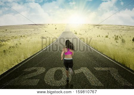 Picture of female athlete running toward sunrise with numbers 2017 on the road