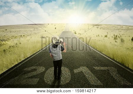 Rear view of young male holding a guitar and standing on the road with numbers 2017