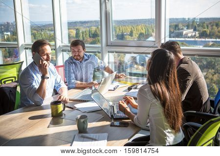 Business people working with documents of their foreign partners in board room in office interior. Businessman talking over mobile phone about signing agreement of contract.