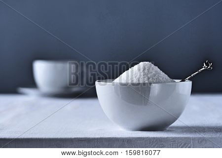 Bowl of sugar on table, tea cup in background