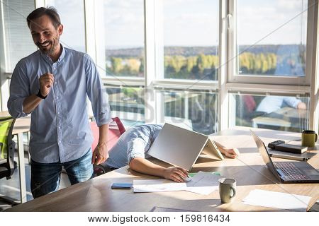 Businessman sleeping on table with laptop computer on or covered after hard working day. Happy men joking during work. Business concept. Break time concept.