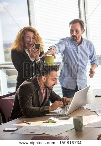 Business people joking in board room in office interior during work time. Happy people making photos and pulling their collegue leg.