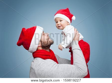 Father With Baby Boy Wearing Santa Hats Celebrating Christmas