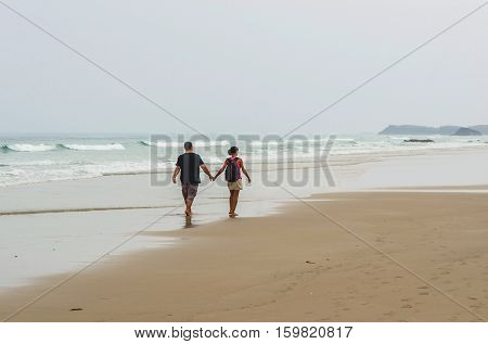Young Couple Beach Stroll